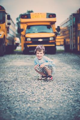Boy at photo session at bus yard